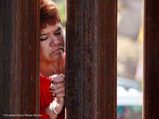 Woman praying at the border between the United States and Mexico