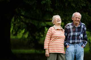 Elderly woman and man laughing together in the park