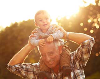 A smiling child being carried on his grandfather's shoulders in a park at sunset