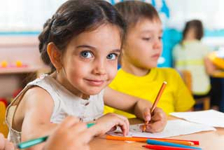 A young female student looks at the camera while working on her school work