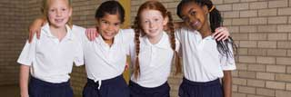 Four children linking arms and smiling in a school