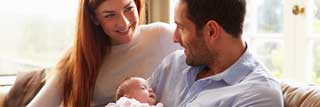 A husband and wife smile at each other while holding their newborn baby
