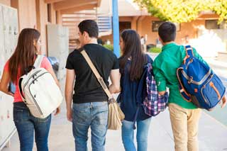 Four high school students walking outside of their school