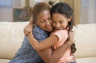 A young girl hugs her grandmother affectionately