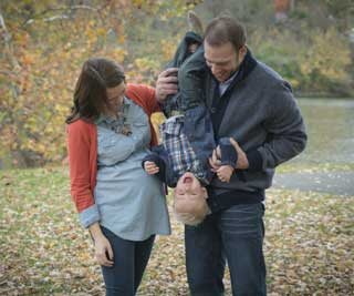 An expectant mother and her husband play with their son in the park on a fall day