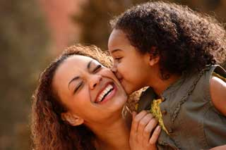 A young girl kisses her laughing and smiling mother on the cheek