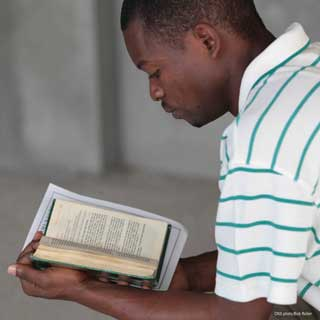 A young African-American man reads the Bible