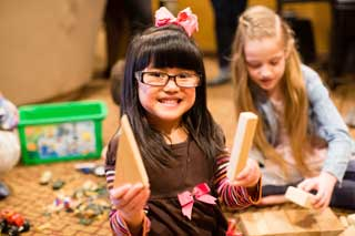 A young girl holding building blocks smiles at the camera while another girl plays behind her