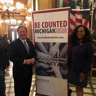MCC President and CEO Paul Long and Michigan Nonprofit Association President and CEO Donna Murray Brown stand next to a Be Counted Michigan 2020 banner at the State Capitol Building