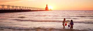 Two young girls play in Lake Michigan while the sun sets behind them, outlining a lighthouse