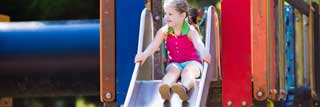 A young girl gets ready to go down a slide at the park