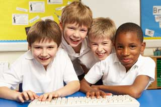 Four Catholic schoolchildren smile while sharing a computer keyboard