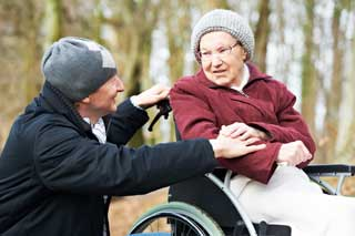 A man comforts an elderly woman in a wheelchair