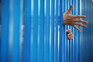 A juvenil's hands reaching through the bars of a jail cell
