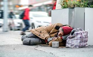 A destitute man sleeping on the sidewalk