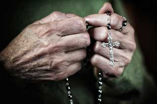 Close up of an older woman's hands praying the Rosary