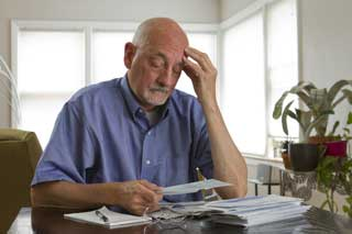 A man contemplates his overdue bills while holding his head in his hand