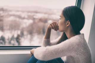 A woman stares contemplatively out of the window
