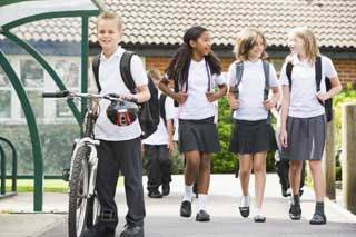 A group of school children in uniform leaving school at the end of the day