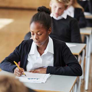 A student sitting at her desk taking an exam