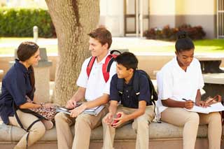 Four students in uniform sitting outside talking and doing homework.