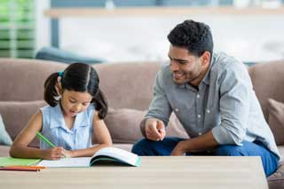 A father helping his daughter with her homework