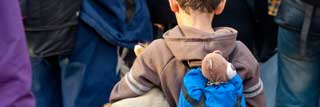 A young boy carrying a stuffed animal under one arm and another in his backpack waits in line