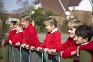 Six happy school children in uniform watching sports from behind a fence