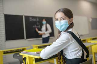 "A young girl wearing a school uniform and protective mask sits in class while her teacher writes ""Back to school"" on the chalkboard."