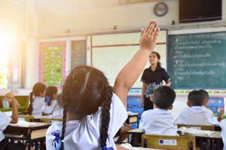 A young girl raises her hand to answer a question in a classroom full of students
