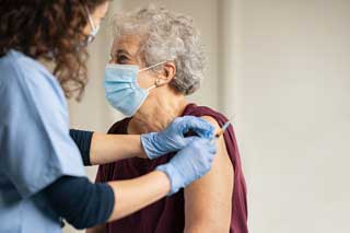 An elderly woman receives the COVID-19 vaccine from her health practitioner