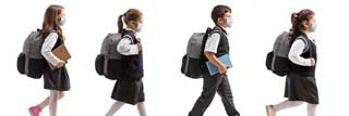 Four children wearing protective masks and school uniforms walking in single file