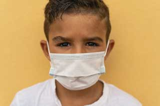 A young boy wearing a facemask standing in front of a yellow wall, looking at the camera