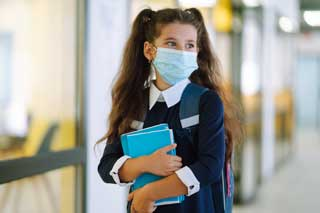 A student wearing a protective face mask and school uniform, carrying her books down a hallway