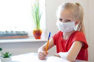 A young girl wearing a protective face mask while doing her school work.